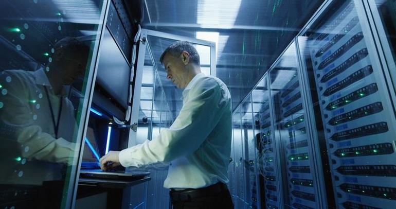 Technician works on a laptop in a data center